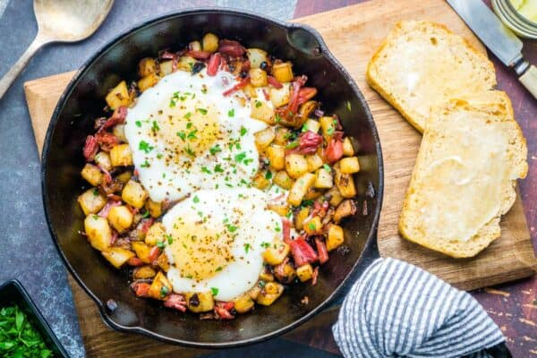 eggs over corned beef hash in iron skillet on board with toasted beer bread slices