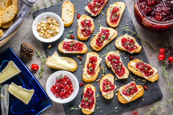 cranberry crostini appetizers on slate tray next to cranberry sauce, walnuts, pomegranate, and brie cheese on blue plate
