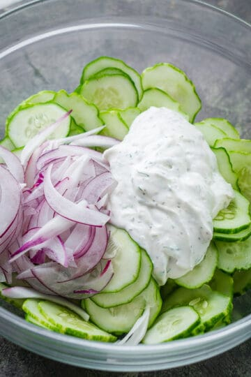 sliced cucumbers, red onions, and cucumber dressing in glass bowl