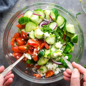 Hands holding silver utensils tossing cucumber salad in glass bowl