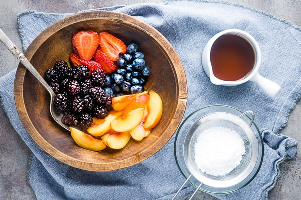 dutch baby toppings: wooden bowl of fresh fruit next to white container of maple syrup next to sifter of powdered sugar on blue linen