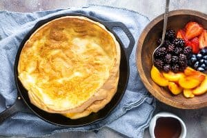 dutch baby pancake in iron skillet on blue linen next to wooden bowl of fresh fruit and white maple syrup container