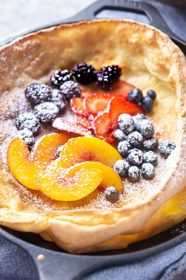 Dutch baby pancake in iron skillet topped with fresh fruit and powdered sugar