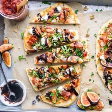 fig prosciutto flatbread pizza slices on parchment paper next to toppings