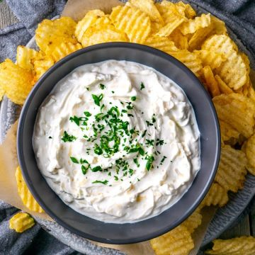French onion dip in black bowl over platter of potato chips on gray linen on gray wood table