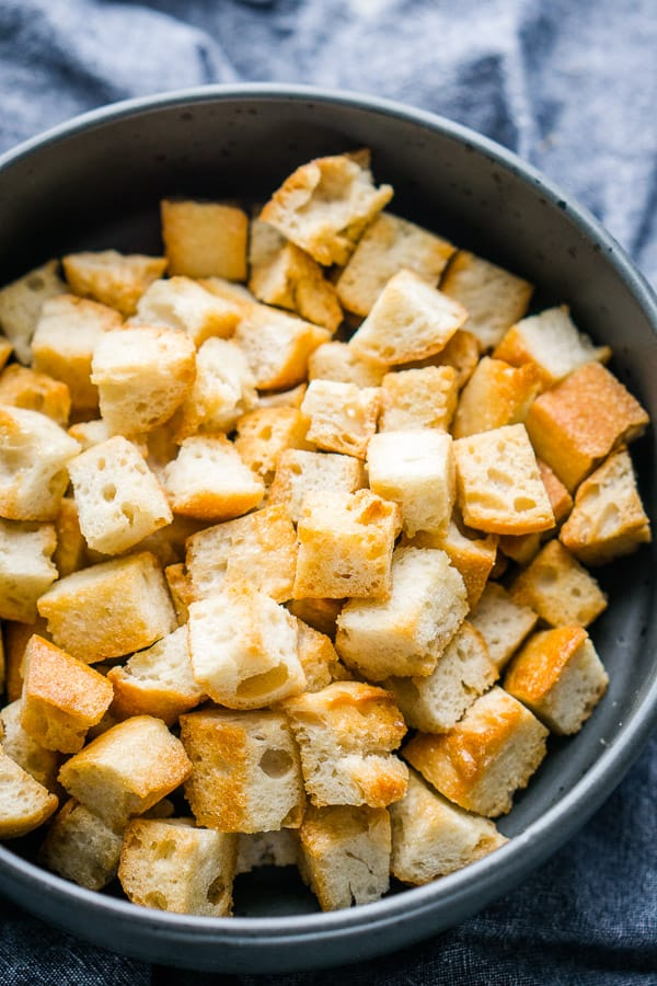 Homemade croutons in gray ceramic bowl on blue linen