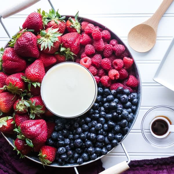 Strawberries, blueberries, and raspberries in colander next to vanilla on spoon, next to white square plate and wooden spoon on white surface with draped purple linen on the side