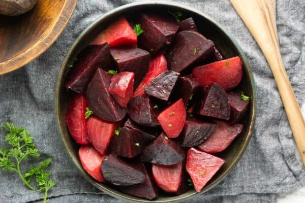 cooked beets in ceramic bowl with parsely garnish next to wooden bowl and spoon
