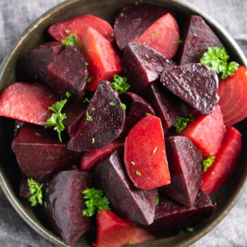cooked beets with parsely garnish in ceramic bowl
