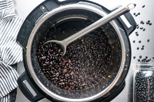 cooked black beans being scooped up from an Instant Pot