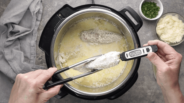 Meat thermometer taking temperature of chicken breast over instant pot with chicken alfredo ingredients in the pot