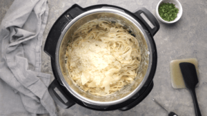 Parmesan cheese piled on top of cooked fettuccine Alfredo inside instant pot