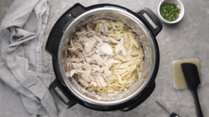 Shredded chicken breast piled on top of fettuccine Alfredo inside instant pot