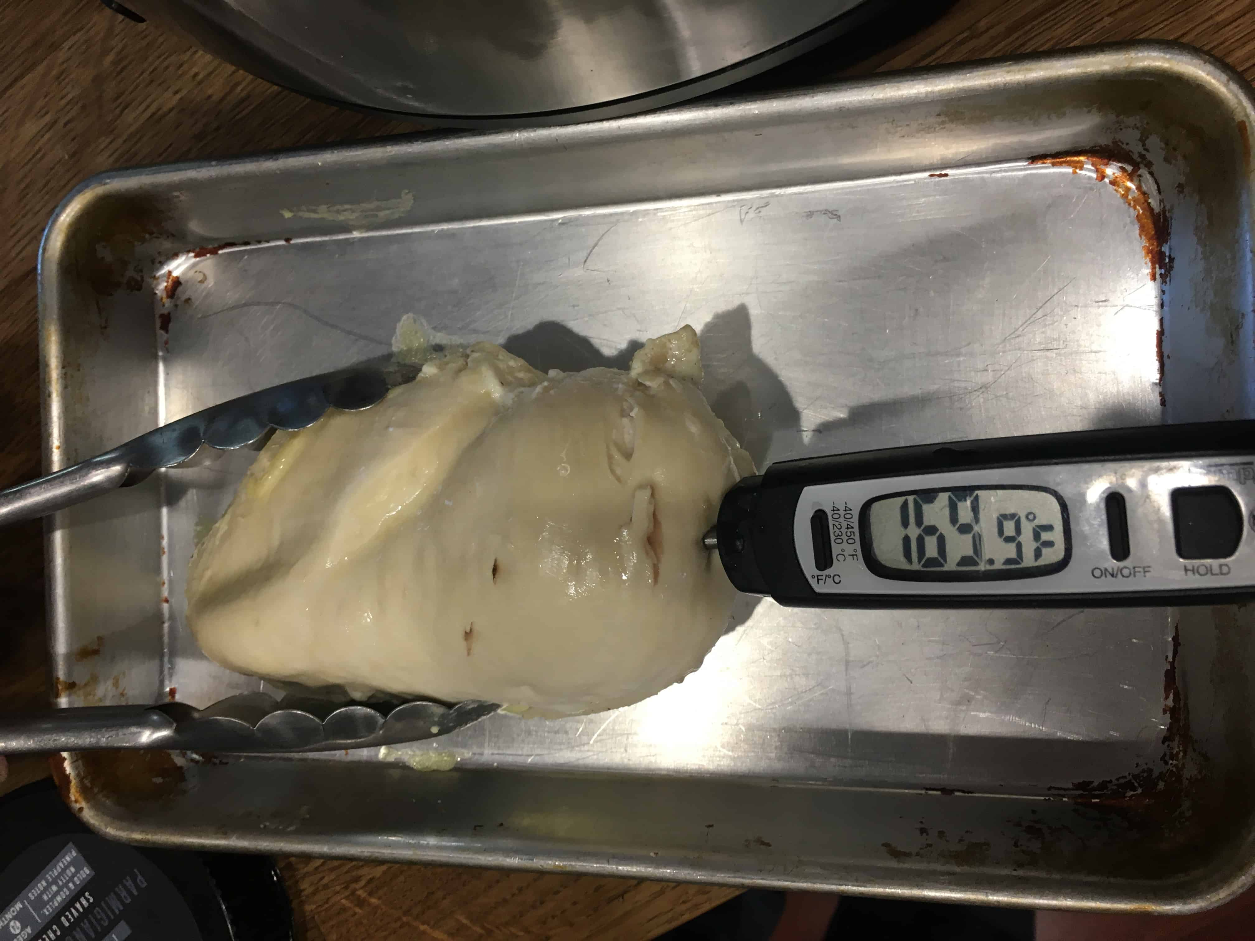Meat thermometer reads 169°F inserted into cooked chicken breast being held by tongs on stainless steel baking sheet
