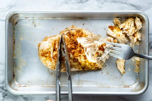 Tons holding chicken breast while fork shreds it onto a baking sheet