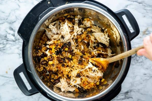 wooden spoons stirring shredded chicken into burrito bowl filling inside the instant pot on white marble surface
