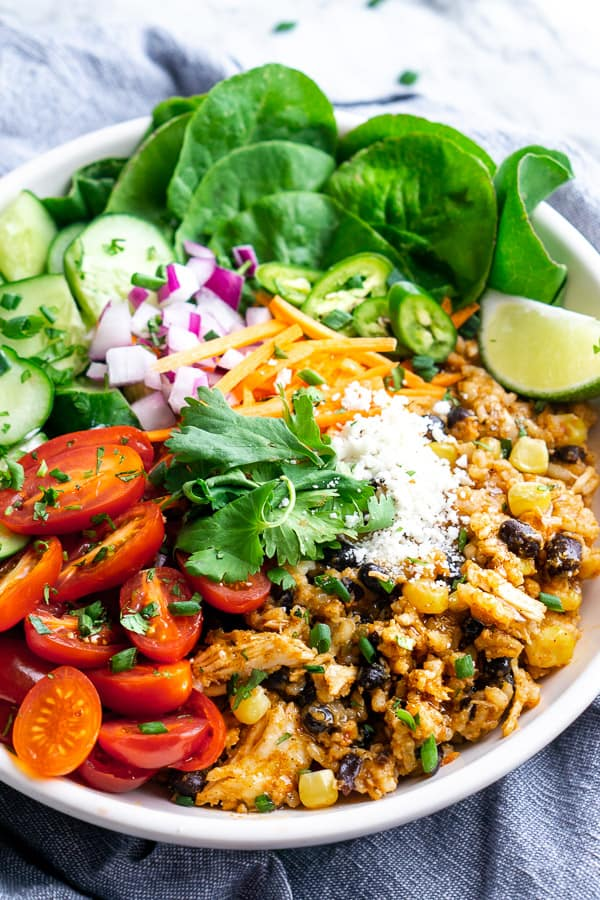 Chicken burrito bowl filling piled with fresh toppings in white bowl on blue linen