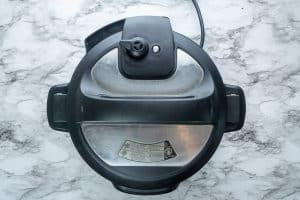 Instant pot with closed lid in pressure cooking mode on marble surface