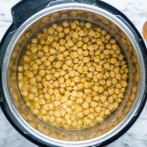 cooked Instant Pot chickpeas (garbanzo beans) in chickpea juice on marble surface with wooden stirring spoon nearby