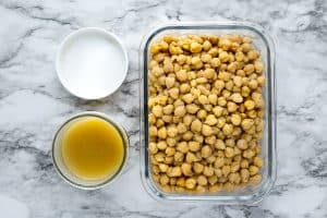 Cooked chickpeas (garbanzo beans) in glass storage container next to chickpea juice in the glass jar with white lid on marble surface