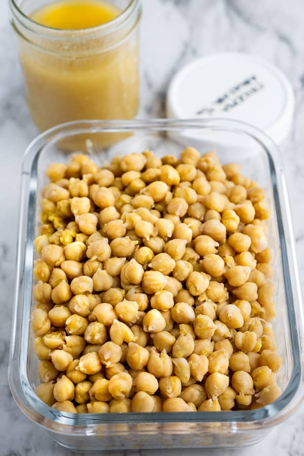 Cooked chickpeas (garbanzo beans) in glass storage container next to chickpea juice in the glass jar with labeled white lid on marble surface