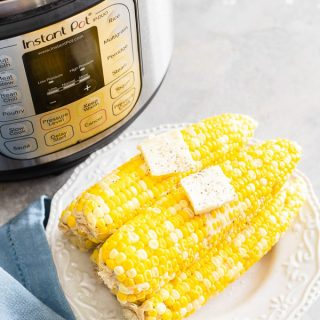 Corn on the cob with butter pats stacked on white plate next to Instant Pot and blue linen on gray surface