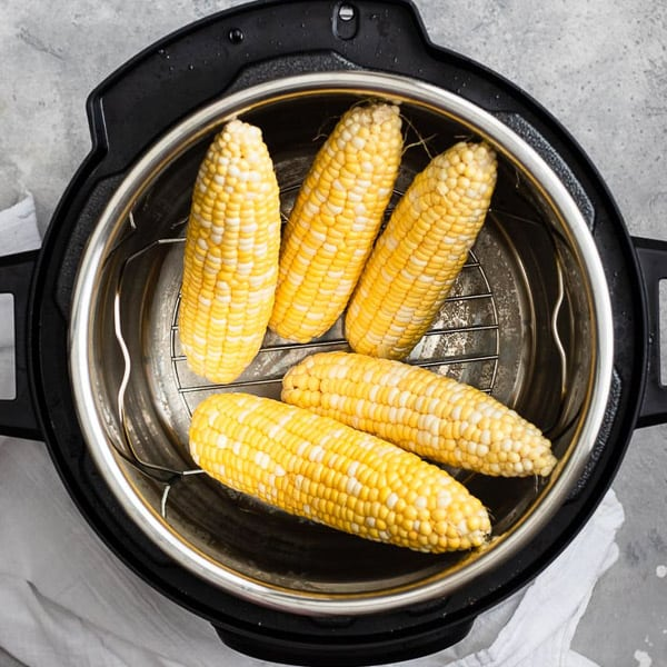 Five ears of corn on the cob stacked upright on a trivet in an instant pot with a draped white linen on a gray surface