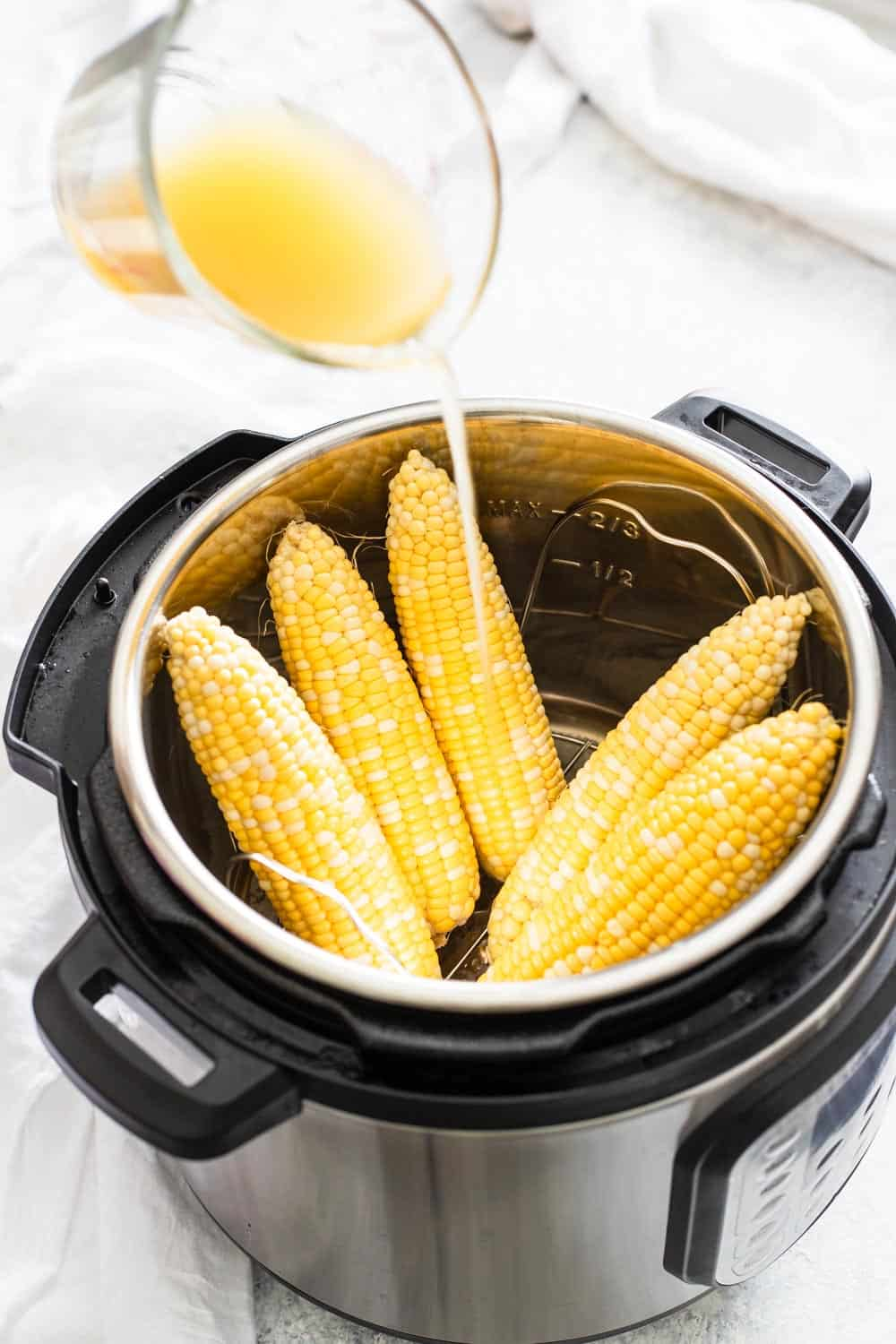 Glass measuring cup pouring broth over corn on the cob in an instant pot on light gray surface