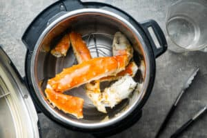 king crab legs on trivet in Instant Pot with water in preparation for pressure cooking