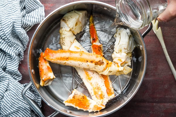 king crab legs on trivet in soup pot with water in preparation for steaming