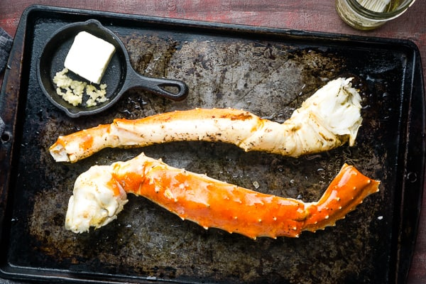 king crab legs on baking sheet next to mini iron skillet with minced garlic and butter