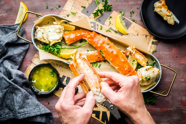 king crab leg being opened by hands after being cut