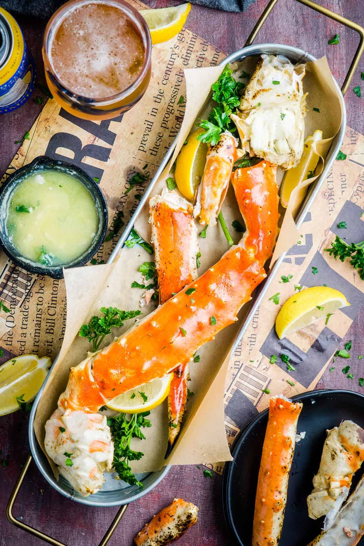 platter of king crab legs next to melted garlic butter skillet, lemons, and glass of beer
