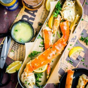 platter of king crab legs next to melted garlic butter skillet, cutting shears, and lemons