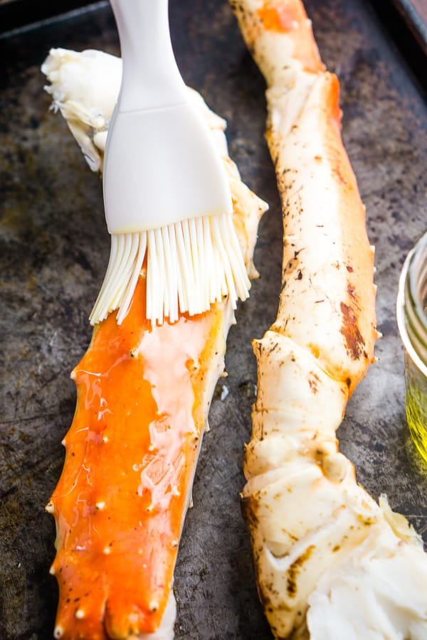 Silicone brush applies olive oil to king crab legs on a baking sheet