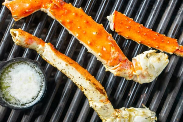 King crab legs and garlic butter in iron skillet on grill