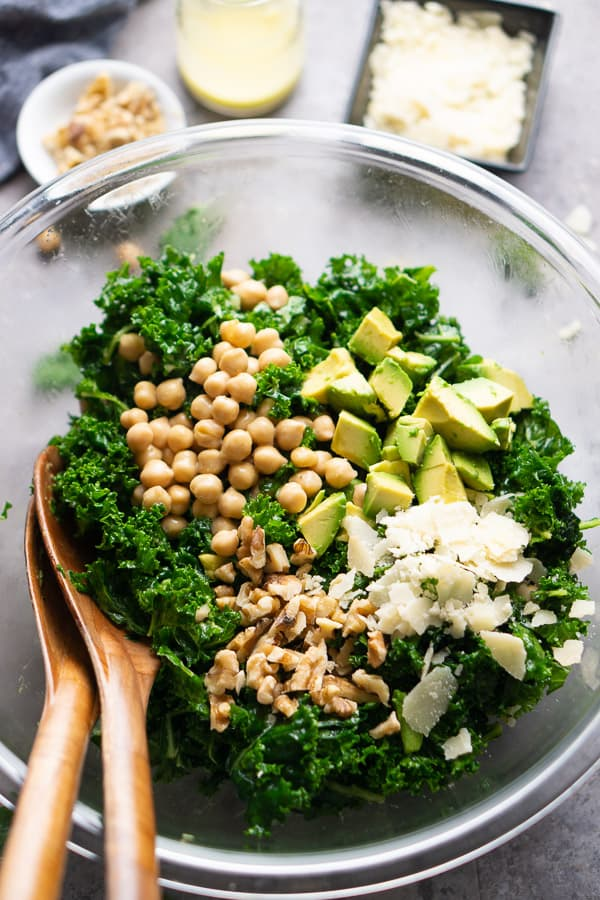 kale salad in glass bowl (kale, chickpeas, walnuts, and shaved cheese) with wood salad tongs. Bowl sits on concrete surface with nearby ingredients (walnuts, parmesan cheese, and vinaigrette).