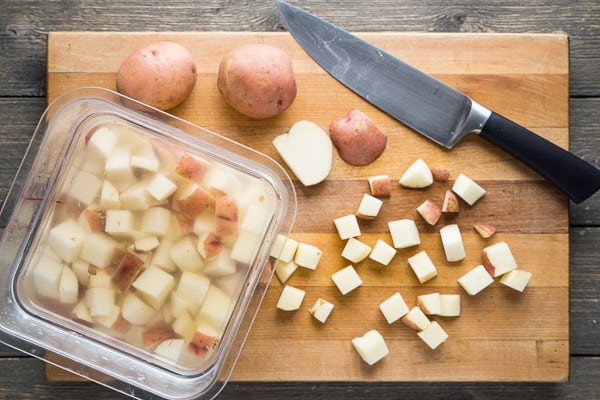 Diced potatoes, whole potatoes, and chef knife on wood cutting board with container of water soaking potatoes on gray wood background