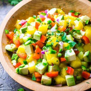 mango salsa ingredients in wood bowl on tan surface