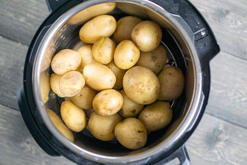 whole potatoes in instant pot on gray background