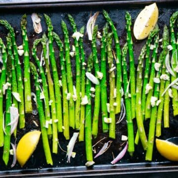 roasted asparagus on baking sheet with lemon wedges, shallots, and garlic