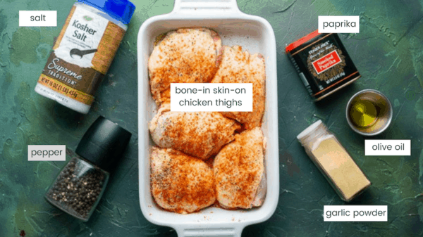 seasoned uncooked chicken thighs in white baking dish next to containers of salt, pepper, paprika, oil, and garlic on green background