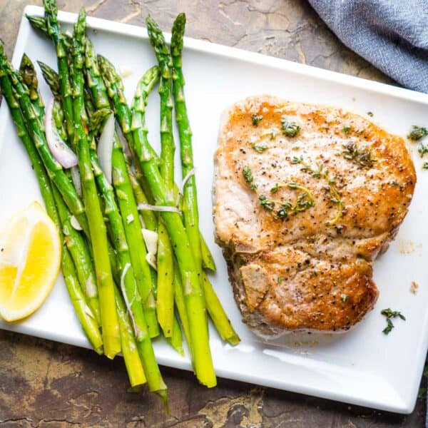 whole pan fried pork chop next to sauteed asparagus on white plate
