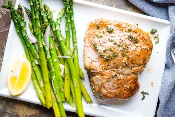 pan fried pork chop next to sauteed asparagus on white plate