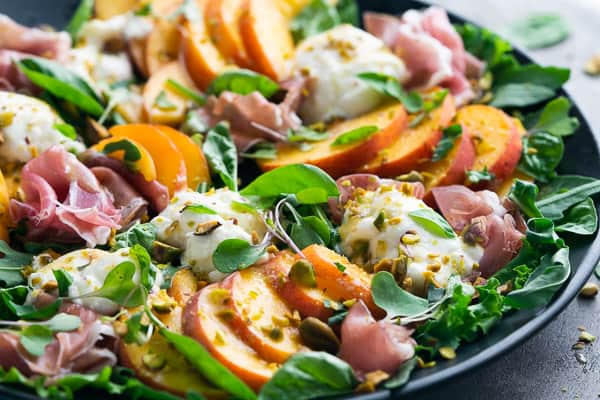 peach burrata salad on black plate on gray background