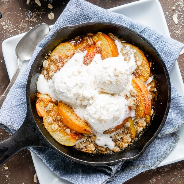 peach crisp topped with vanilla ice cream in iron skillet on blue linen-covered white plate on brown surface