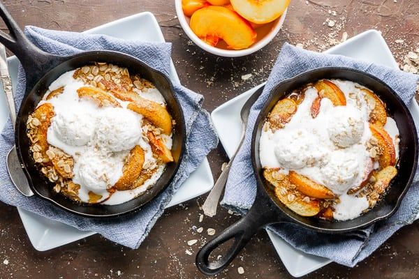 two peach crisps topped with vanilla ice cream in iron skillets on blue linen-covered white plates on brown surface