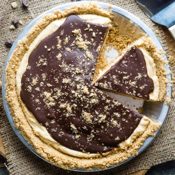 peanut butter pie slices in aluminum pie tin next to pie server on burlap lined brown wooden plate with chocolate chips scattered
