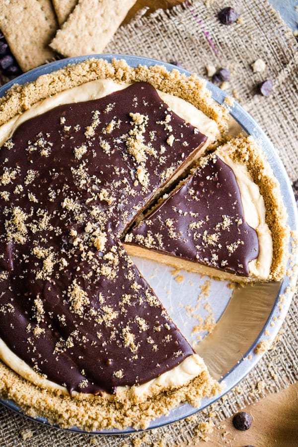 peanut butter pie slices in aluminum pie tin on burlap and brown wood background with graham crackers and chocolate chips scattered about
