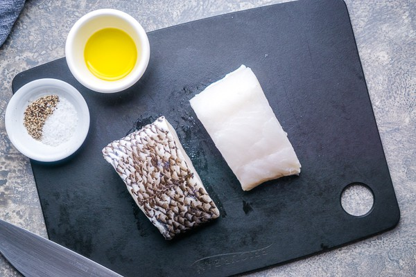 2 uncooked sea bass filets on black cutting board next to ramekins of olive oil and seasonings